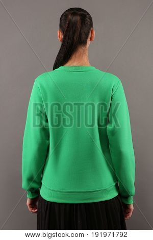 Back of Young hipster girl wearing blank lime green cotton sweatshirt with copy space for your design or logo mock-up of ltemplate womens hoodie grey wall in the background