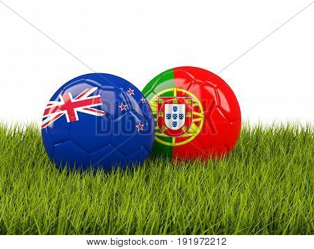 Two Footballs With Flags Of New Zealand And Portugal On Green Grass