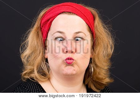 Attractive red haired lite overweight european mature woman with red scarf in hair looking squint and forming kiss mouth - studio shot on dark background