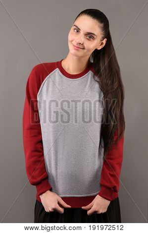 Young hipster girl wearing blank grey and burgundy cotton sweatshirt with crew neck and raglan sleeves with copy space for your design or logo mock-up of ltemplate womens hoodie
