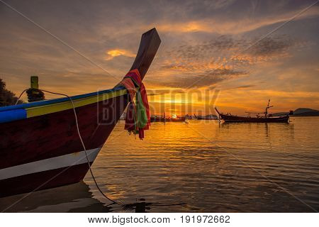 Beautiful dramatic sunrise at Rawai beach with andaman long tailed boat southern of thailand floating on clear sea water with sun shine in phuket