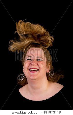 Attractive red haired lite overweight european mature woman with funny hair style - moving the head, studio shot on dark background