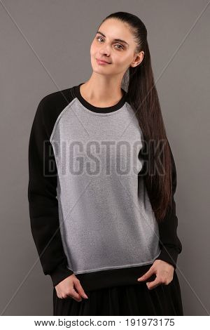 Young hipster girl wearing blank grey and black cotton sweatshirt with crew neck and raglan sleeves with copy space for your design or logo mock-up of ltemplate womens hoodie