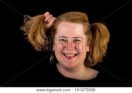 Attractive red haired lite overweight european mature woman with funny hair style - pulling her hair, studio shot on dark background
