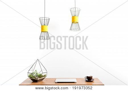 closed notebook, cup of coffee and flower pot on desk surface. Chandeliers are hanging over workplace. Isolated
