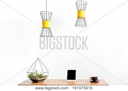 tablet, coffee mug an on holder and vase with domestic flowers on desk. Modern ceiling lams hanging over place of work. Isolated