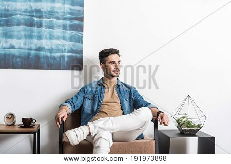 Short morning break. Cheery young man with beard is sitting on stylish armchair in his room and looking aside to distance
