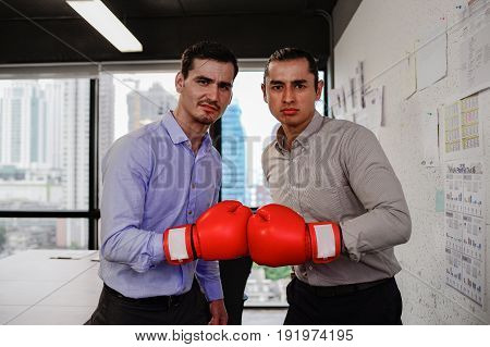 Two businessman look camera with boxing gloves in the office