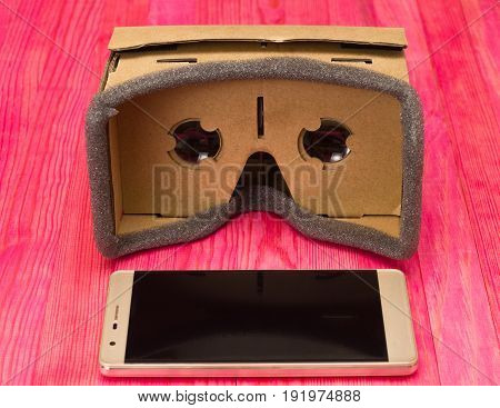 cardboard virtual reality glasses on pink wood front view