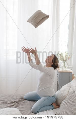 Side view of pregnant woman sitting on bed throwing up the pillow and having fun.