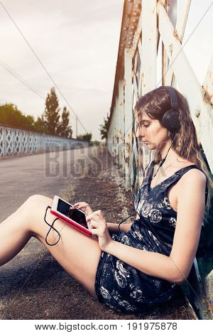 young beautiful woman listening music with tablet and sitting on the road