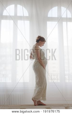 Side view of pregnant woman in elegant dress standing on bench at window.