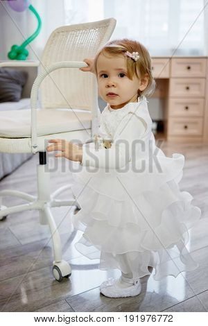 Little girl in white holiday dress stands holding hand on armrest of armchair.
