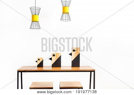 Close up of three decorated birds for books of different sizes on desk top with two chairs beside. Modern chandeliers hanging over. Isolated