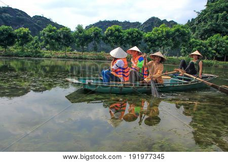 Trang An Ninh Binh Vietnam - OCT 05 2014 The tourists are travelling by boat in the river. Trang An landscape complex has been recognised as UNESCO World Heritage site