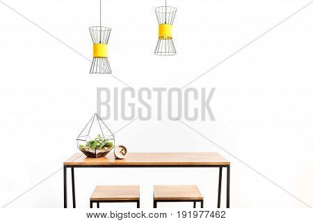 Close up of stylish flowerpot and alarm clock on table with two stools beside. Chandeliers hanging over workplace. Isolated