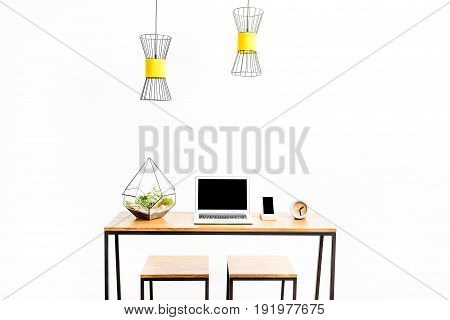Close up of laptop and smartphone with clock and flowerpot on table with two chairs. Ceiling lamps hanging over workplace. Isolated