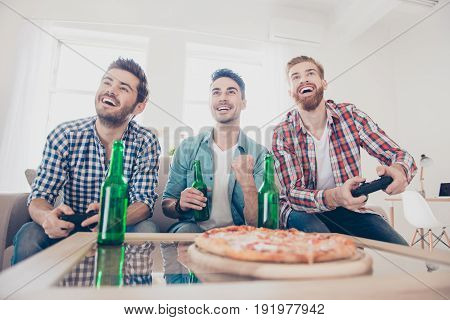 We Are Champions! Bachelor Men`s Life. Low Angle Of Three Joyful Men, Sitting On Sofa And Playing Vi