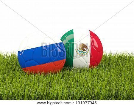 Two Footballs With Flags Of Russia And Mexico On Green Grass