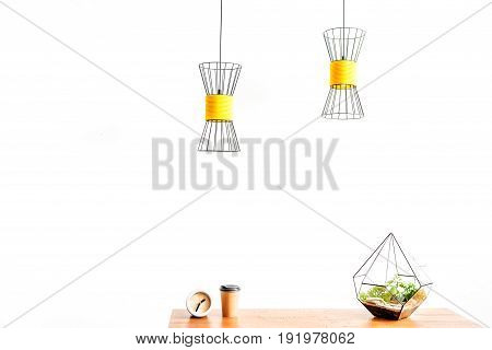 Close up of plastic cup for coffee with alarm clock and vase with domestic plant on desktop. Chandeliers hanging over workplace . Copy space in left side and isolated