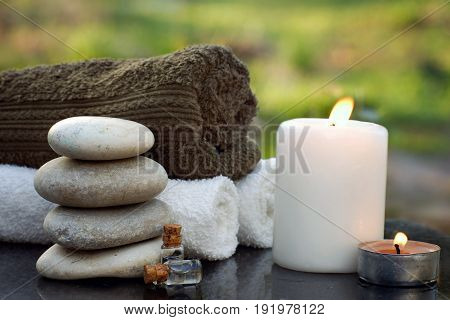 Spa still life with towels a burning candle bath oil and massage stones against the backdrop of a green garden.