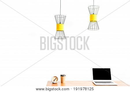 Close up of laptop from one side and alarm clock with plastic coffee glass from other side of table surface. Two chandeliers hanging over workplace. Copy space in left side and isolated