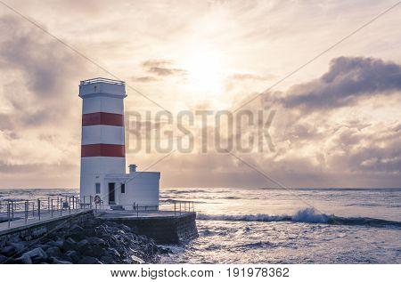 Old lighthouse in Gardur, Iceland. Cloudy Sky and choppy sea