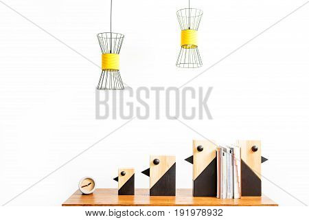 Close up of little alarm clock and four decorative birds with pile of notebooks between them on table surface. Chandeliers hanging over workplace. Isolated