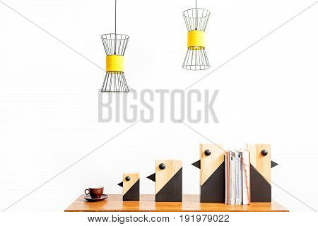 Close up of coffee cup, decorative birds and pile of books between them on table. Designer chandeliers hanging over place of work. Isolated