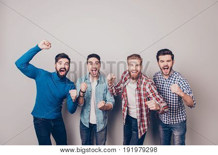 Champions! Four Amazed Young Men Are Standing And Gesturing For The Victory On Pure Background In Ca