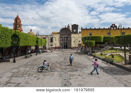 San Miguel de Allende Mexico - May 29 2014: People in a square in the historic center of the city of San Miguel de Allende Mexico.