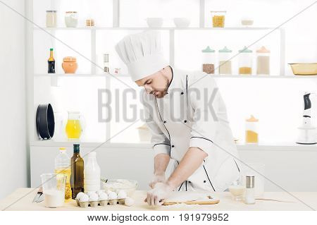 Man Chef  baking dough with rolling pin in the kitchen