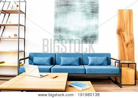 Living room with long comfortable sofa and huge square picture above it. High stand with shelves and designer wardrobe from different sides of couch and table with laptop on it in front of