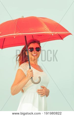 Beauty of ginger hair concept. Portrait of beautiful happy redhead adult plus size woman holding red umbrella wearing sunglasses in heart shape.