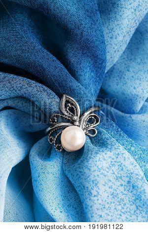 Elegant vintage pearl ring on blue draped silk closeup