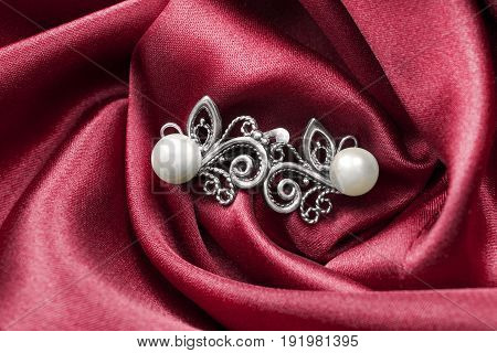 Elegant silver pearl earrings on red crumpled satin closeup