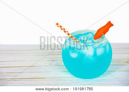 blue cocktail drink in fishbowl on whitewashed wood with candy goldfish garnish and checkered orange and white straw