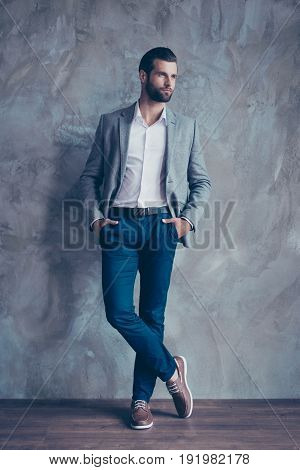 Full Size Portrait Of Stylish Young Bearded Man Standing On Gray Concrete Background. He Is In A Sui