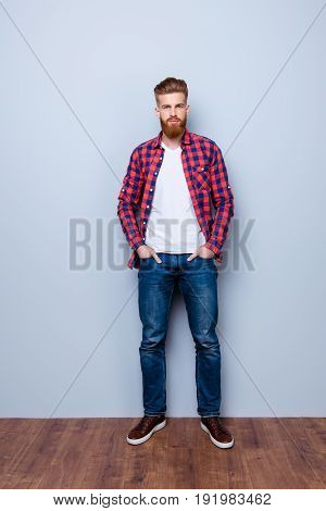Successful Young Stylish Red Bearded Freelancer In Bright Casual Shirt And Jeans On Pure Background.