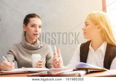 Portrait of two beautiful young girlfriends sitting in modern coffee shop interior and talking with happy smiles. Successful attractive women friends chatting in cafe during coffee break.