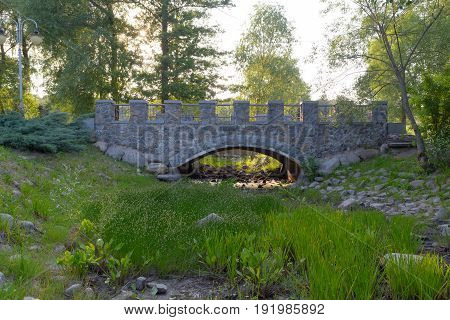 The view on bridge moon gate with green grass and round stones