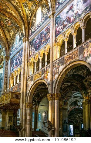 Parma, Italy - November 29, 2013: The Basilica Cathedral inside the side walls of the nave with frescoes of the Ancient and New Testament