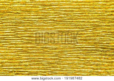 Gold Texture of Embossed Paper. Gold Paper Texture Background. Abstract background with deep grooves in the texture of corrugated paper. Pattern of horizontal grooves