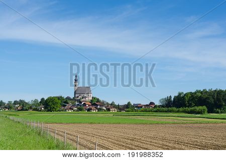 Idyllic and pastoral landscape in Bavarian township Anger with old church of Assumption of the Blessed Virgin Mary