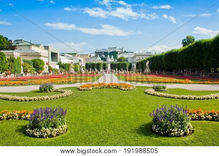 Beautiful View Of Famous Mirabell Gardens With The Old Historic Fortress Hohensalzburg In The Backgr