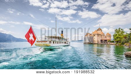 Scenic panorama view of traditional paddle steamer excursion ship with historic Chateau de Chillon at famous Lake Geneva on a sunny day with blue sky and clouds in summer Canton of Vaud Switzerland