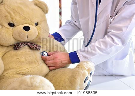 Pediatrician Doctor Behind Table Auscultating Teddy Close Up