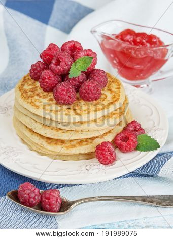 Stack of pancakes decorated with ripe berries of large red raspberry and sauceboat with jam in the background of a checkered blue-and-white napkin