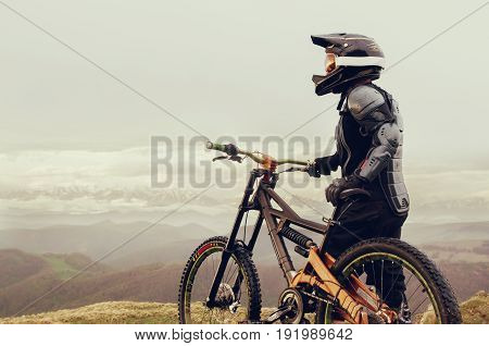 The rider in full protective equipment on the mtb bike resting stands on a rock against the backdrop of a ridge and low clouds and looks at the landscape.