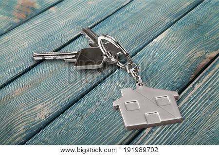 Key silver home badge on table background